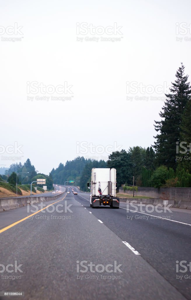 WHite semi truck tractor running on devided freeway with green trees stock photo