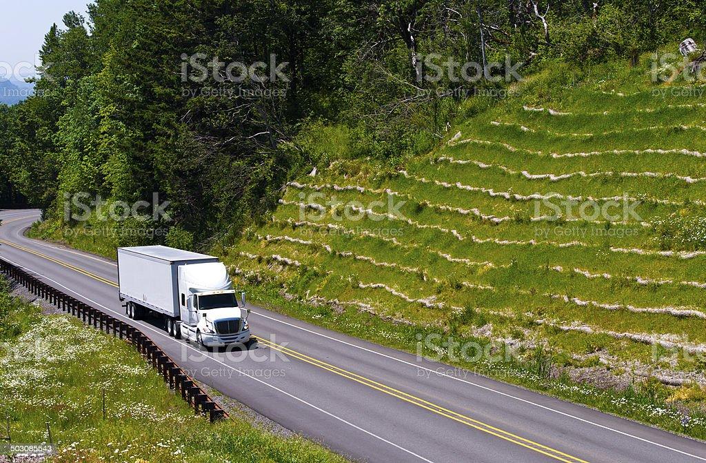 White semi truck trailer on green hill high way stock photo