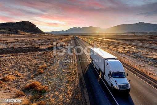 istock White Semi-Trailer Truck Heading down a four-lane Highway at Dusk 1289928297