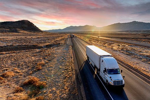 White Semi-Trailer Truck Heading down a four-lane Highway at Dusk delivering a load in the southeastern Utah desert on interstate 70 east bound