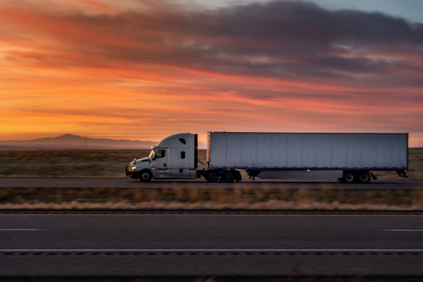 White Semi-Trailer truck speeding down I-70 Interstate under a rural Utah Sunset stock photo