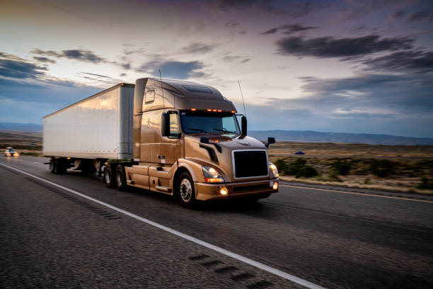 White Semi-Truck Speeding down a four lane highway with a dramatic sunset in the background and headlights on stock photo
