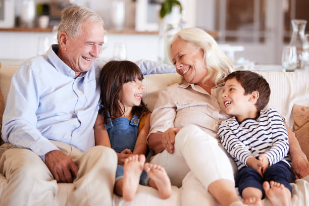White senior couple and their grandchildren sitting on a sofa together smiling at each other stock photo