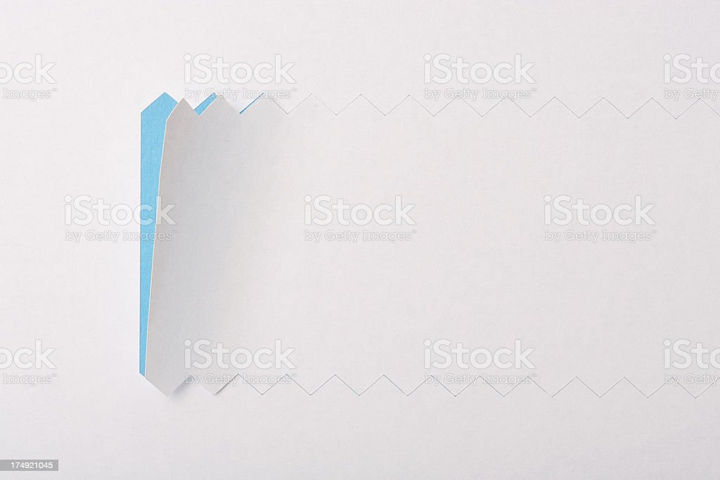 White serrated paper reveals blue underneath royalty-free stock photo