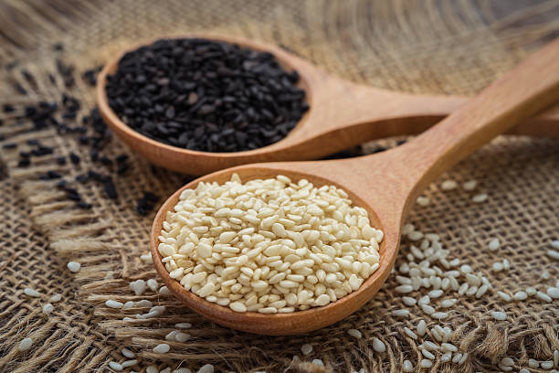 white sesame and black sesame seed on wooden spoon - sesame stock photos and pictures