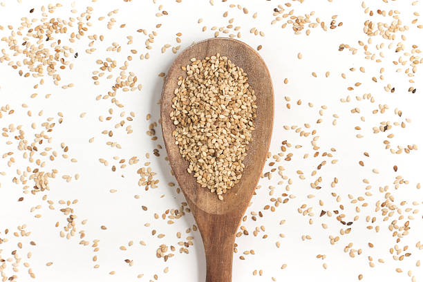 white sesame into a spoon - sesame stock photos and pictures