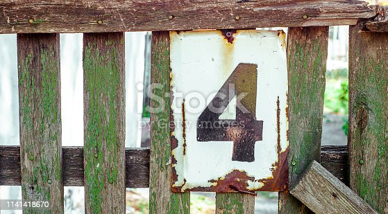 White Shabby And Rusty Metal Plate With Black Number Four, Nailed On Green Old Fence