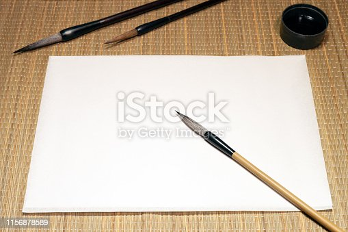 White empty sheet of washi paper, chinese bamboo calligraphy brushes and inkwell on cane matting background, with free space for text