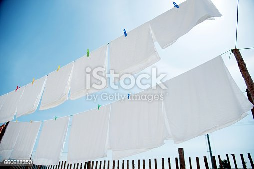 istock White sheets and towels hanging on clotheslines 660688350