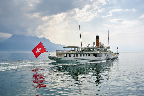 A white ship, a ship with the Swiss flag floats on a mirror lake of Geneva.
