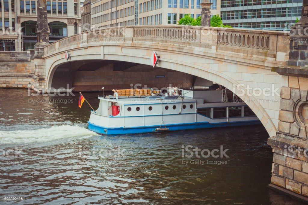 White ship passing under the Friedrichsbrucke bridge on Spree river in rainy day stock photo