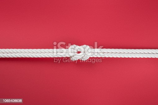 White ship ropes connected by reef knot. On red background