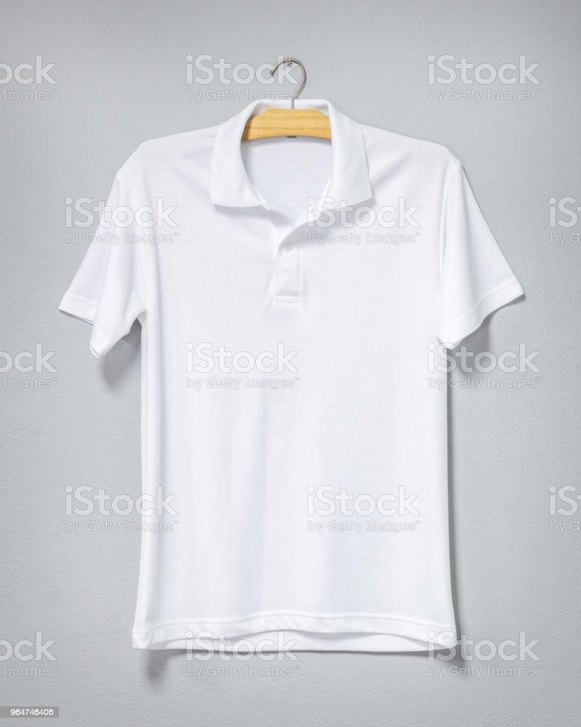 Camisa blanca colgada de la pared de cemento. Camiseta en blanco para la impresión. Vista frontal. - foto de stock