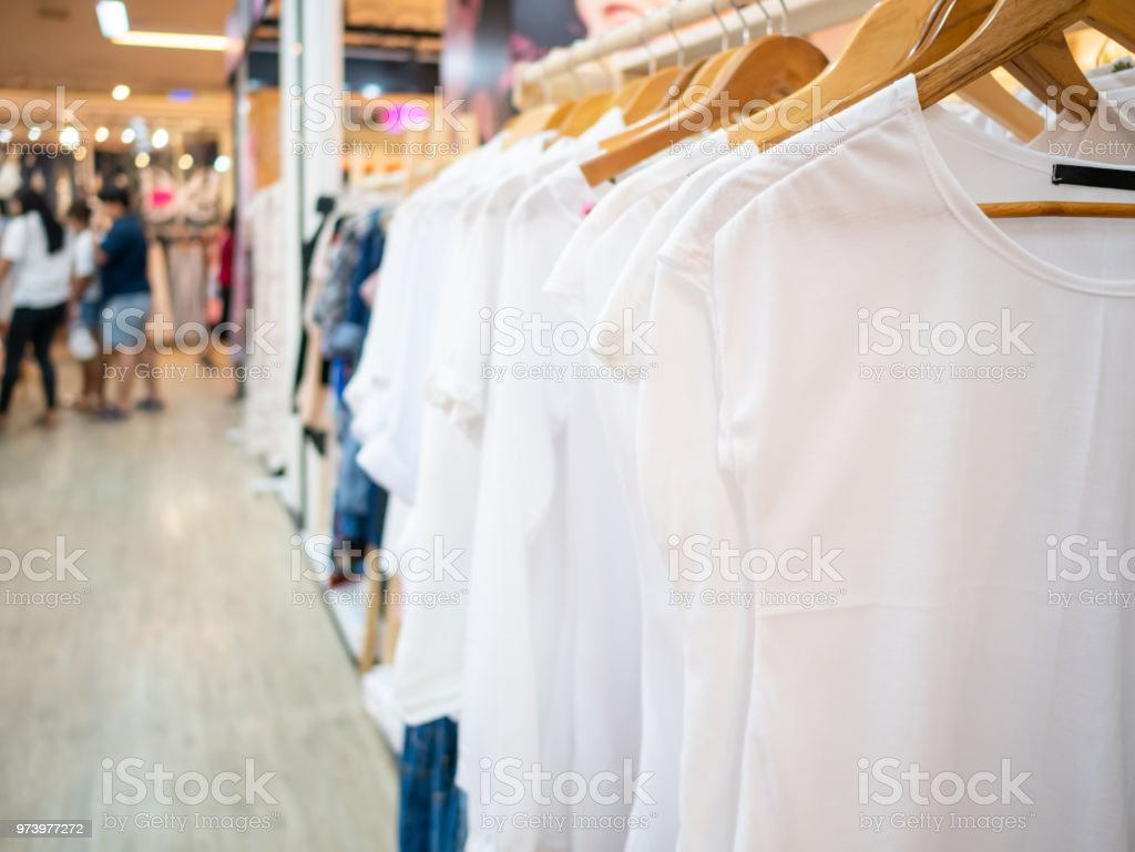 5a7cc921ef02 White shirt women s dresses on hangers in a retail shop clothing store.  Fashion and shopping concept - Stock image .