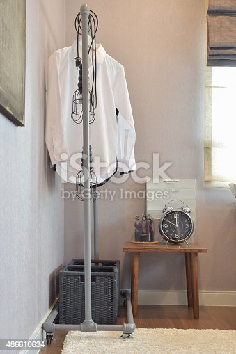 istock white shirts hanging on standing rail and decorative alarm clock 486610634