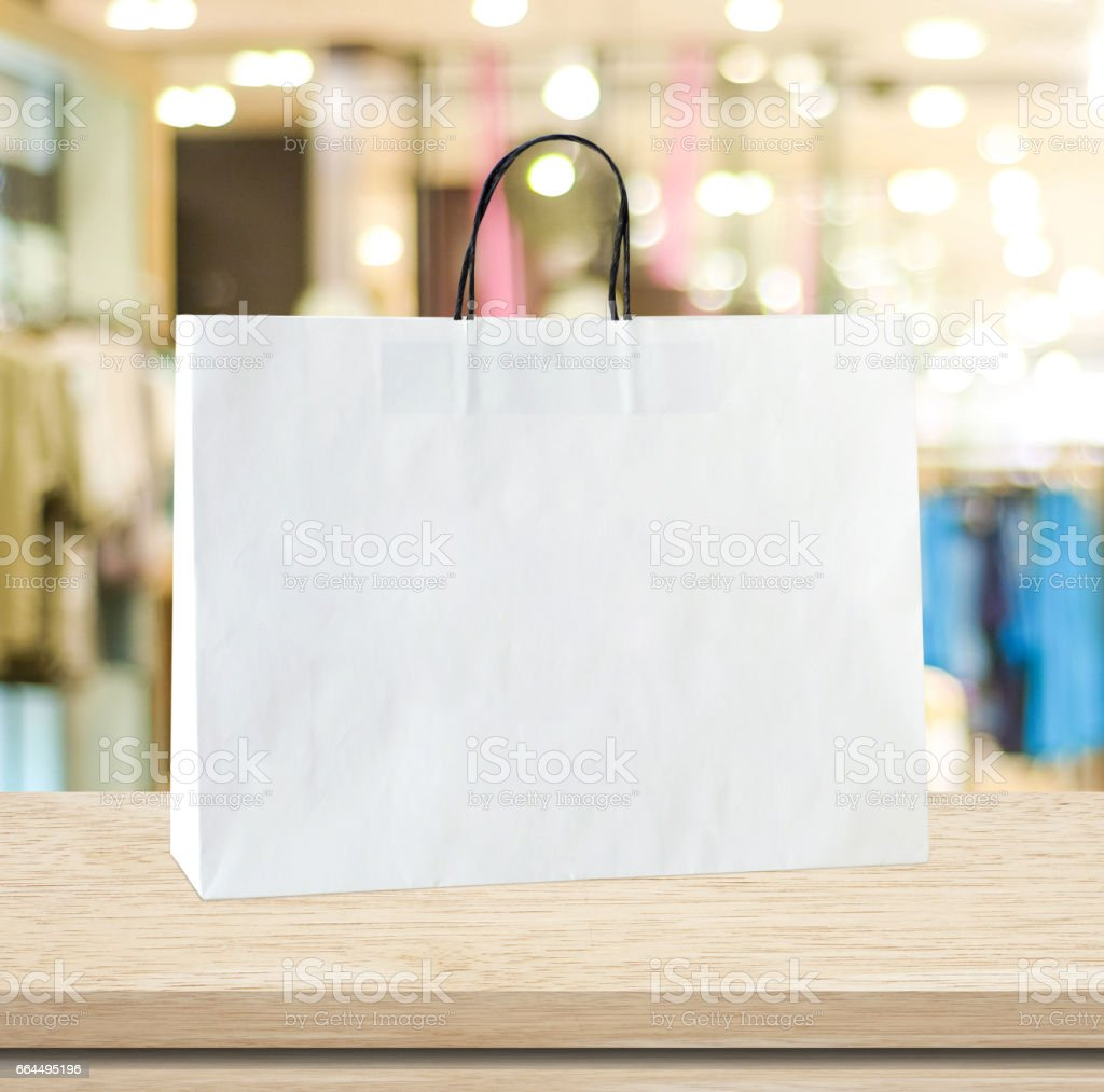 White shopping bag on wooden table over blurred store background, business, template, retail, sale, product display montage stock photo