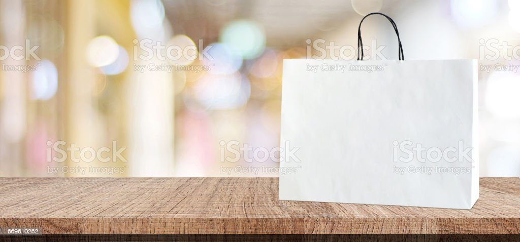 White shopping bag on wooden table over blurred store background, business, template, product display montage background, banner stock photo