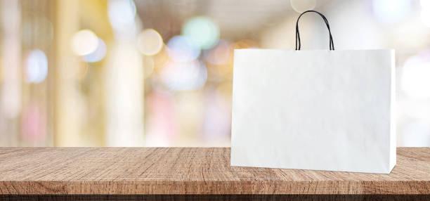 Bolso de compras blanco sobre mesa de madera sobre fondo de tienda borrosa, negocio, plantilla, Fondo de montaje de la exhibición productos, banner - foto de stock