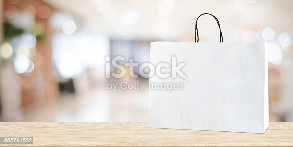 istock White shopping bag on wooden table over blurred store background, business, template, product display montage background 885791532