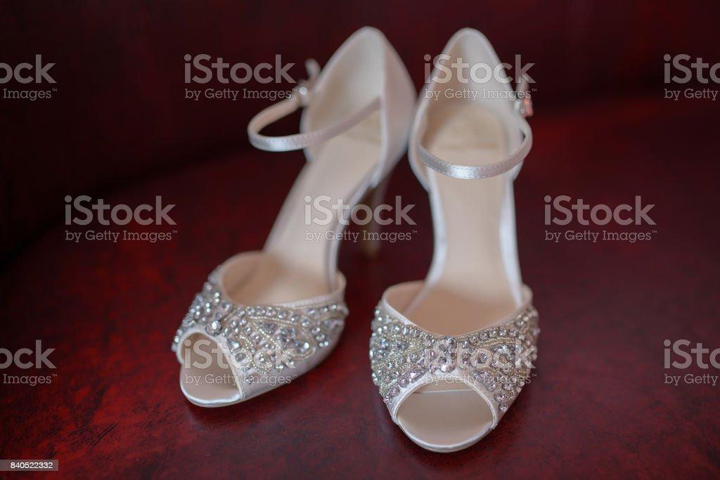 Zapatos peep novia seda blanco con pedrería y abalorios delicados, muestra plenamente, en par, sobre un fondo rojo oscuro - foto de stock