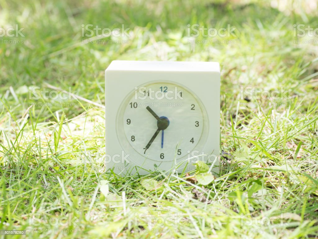 White rectangle simple clock on lawn yard, 10:35 ten thirty five...