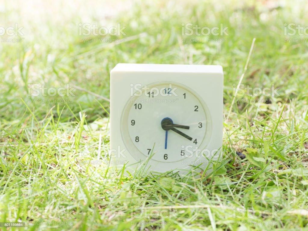 White simple clock on lawn yard, 3:20 three twenty o'clock stock photo