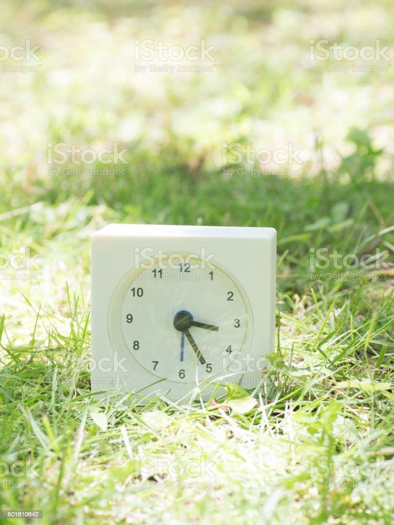 White rectangle simple clock on lawn yard, 3:25 three twenty five...