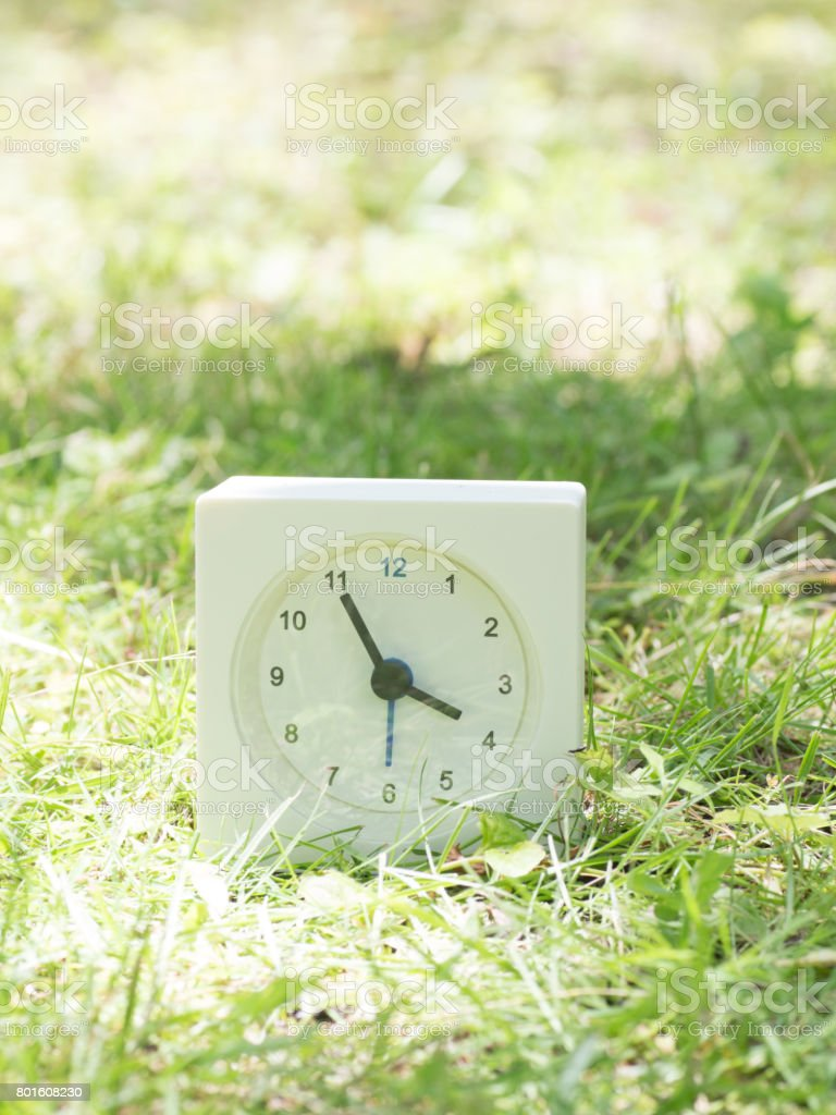 White rectangle simple clock on lawn yard, 3:55 three fifty five...