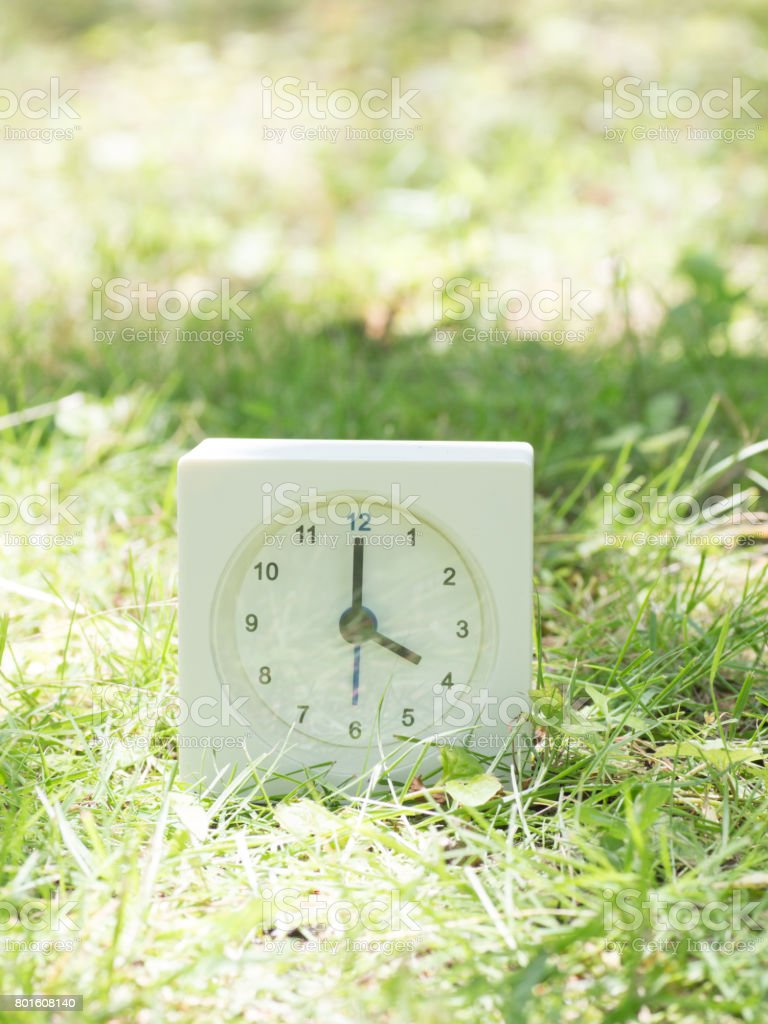 White rectangle simple clock on lawn yard, 4:00 four o\'clock