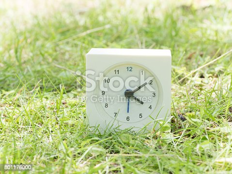istock White simple clock on lawn yard, 4:10 four ten o'clock 801176000
