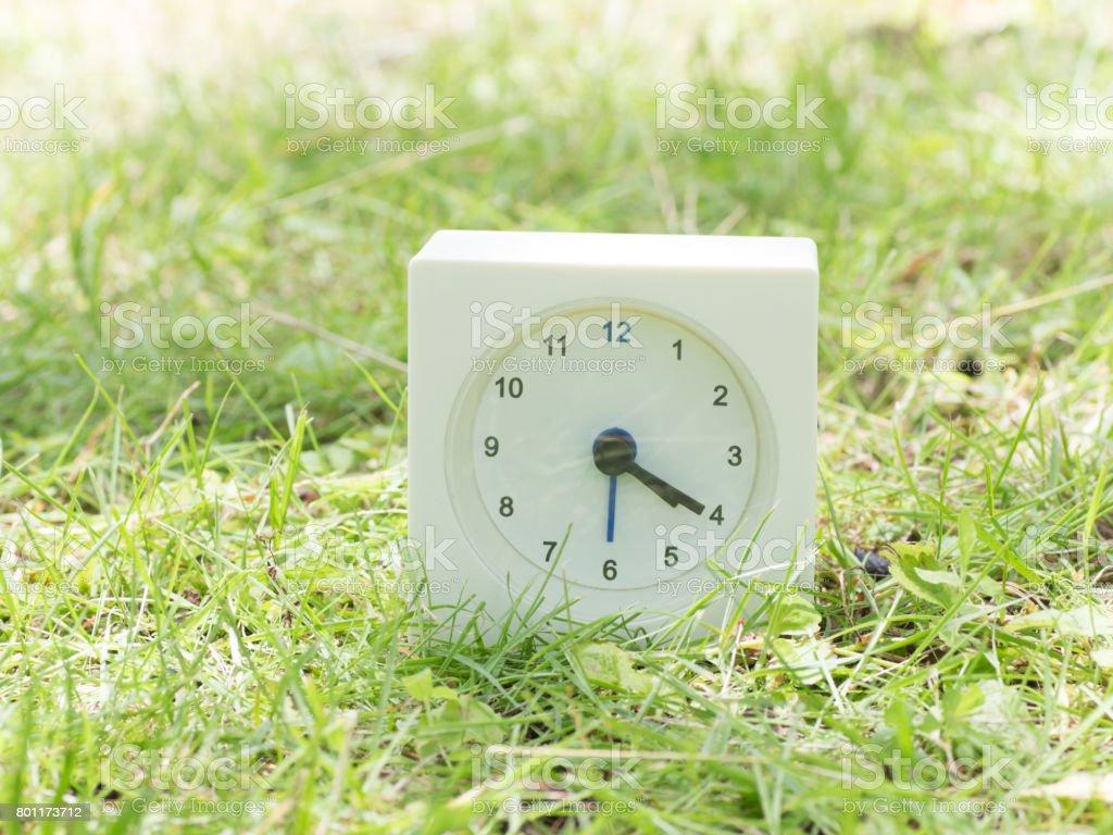 White simple clock on lawn yard, 4:20 four twenty o'clock stock photo