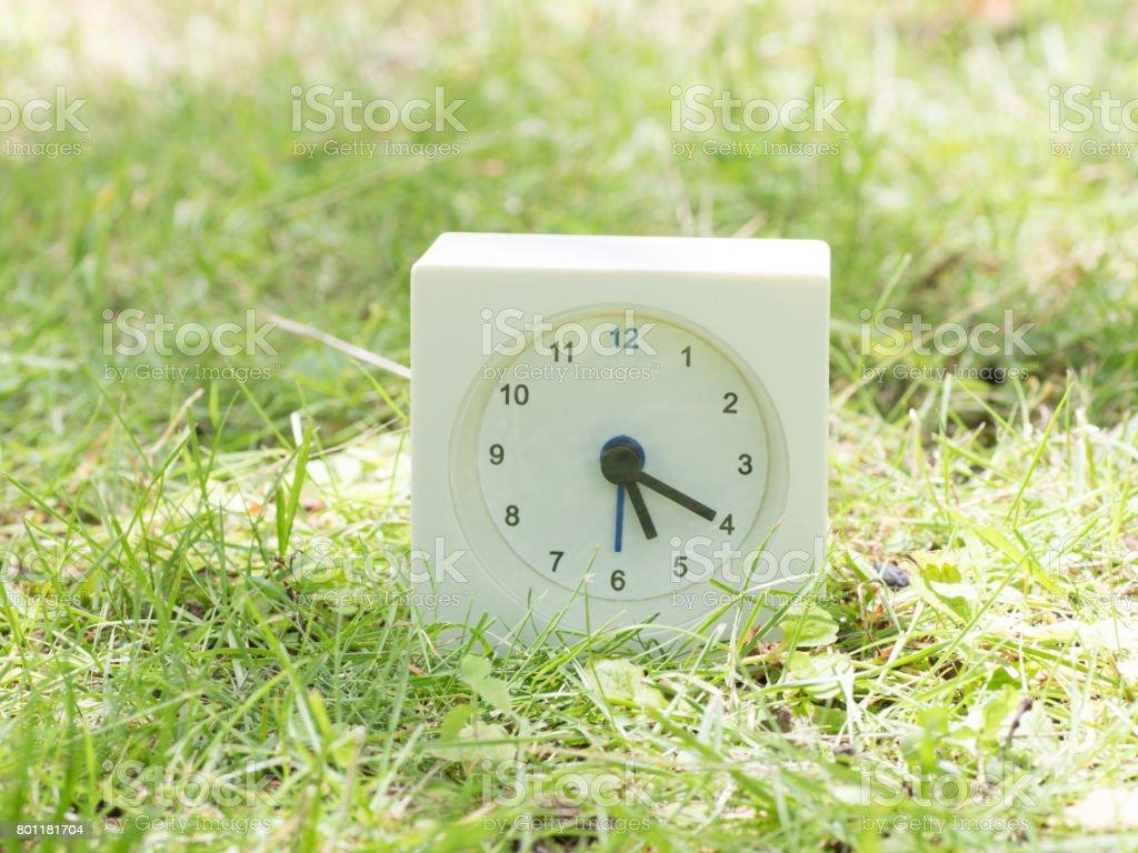 White simple clock on lawn yard, 5:20 five twenty o'clock stock photo