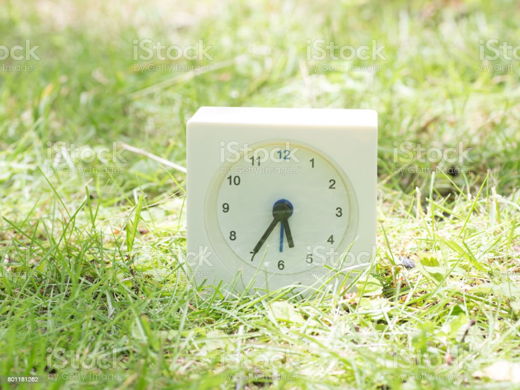 White rectangle simple clock on lawn yard, 5:35 five thirty five...