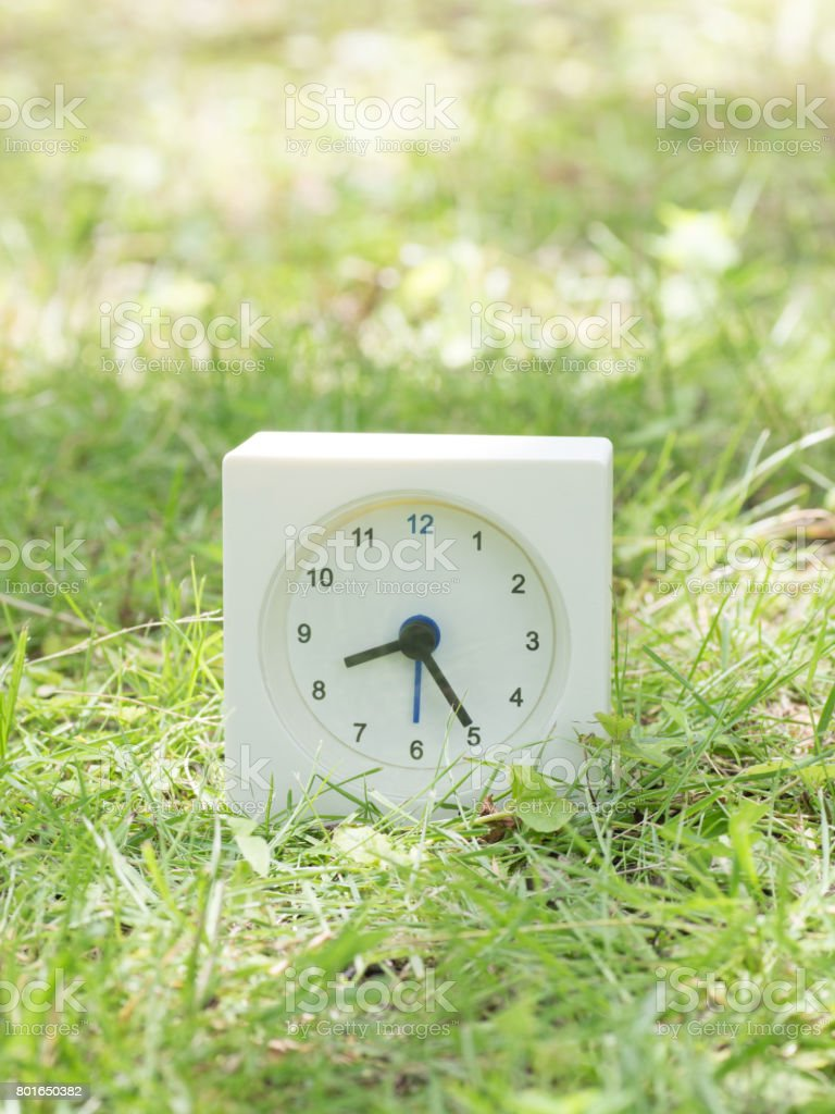 White rectangle simple clock on lawn yard, 8:25 eight twenty five...