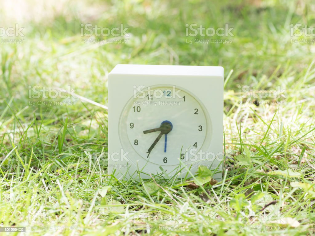 White rectangle simple clock on lawn yard, 8:35 eight thirty five...