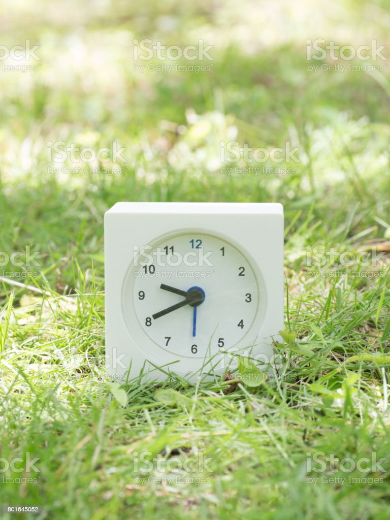White rectangle simple clock on lawn yard, 9:40 nine forty o\'clock