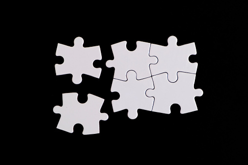 Jigsaw puzzle pieces on black background. Four Puzzle Pieces Connected, copy space for your text.