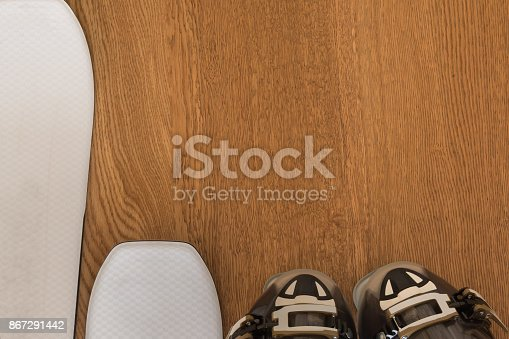 White Ski and Black Ski Boot on Rustic Wooden Background with Copyspace