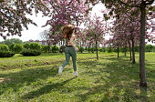 1 white slender athletic girl running among the flowering trees in the Park, blooming Apple trees, outdoor training, brown-haired girl with long hair in sportswear from the back