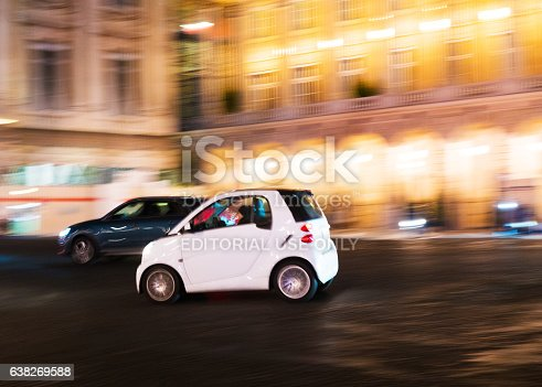 Paris, France - January 6, 2016: White Smart car speeding around Place de la Concorde in Paris at night - panning blur motion effect. The Smart is a  micro car or subcompact which have many advantages due to its small size as been easy to park, lower consume and easy to drive.