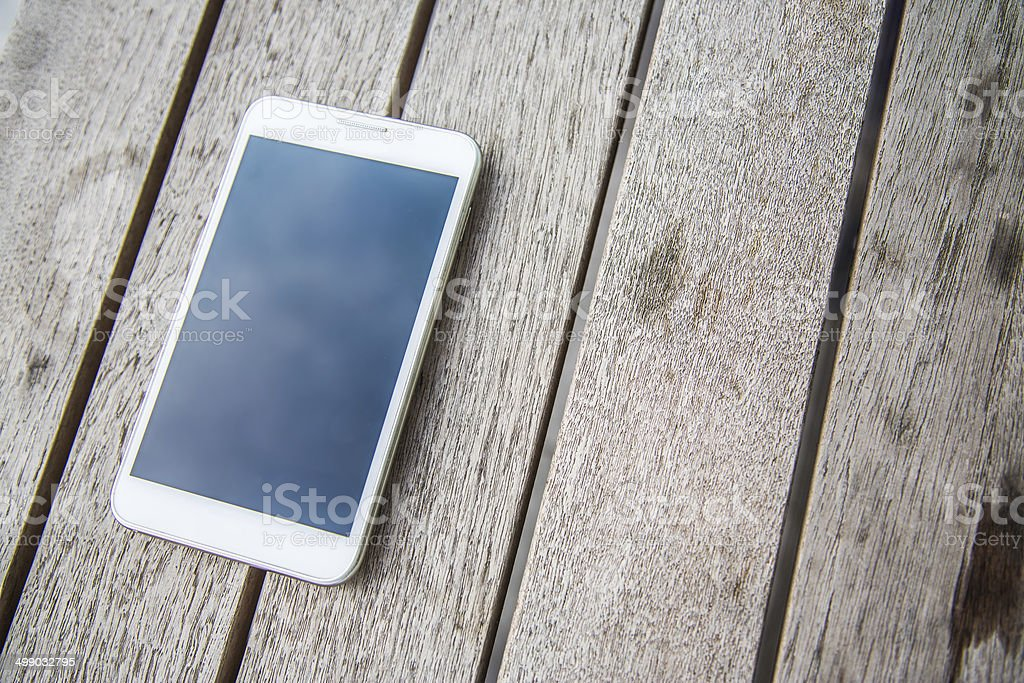White smart phone on the wooden table stock photo