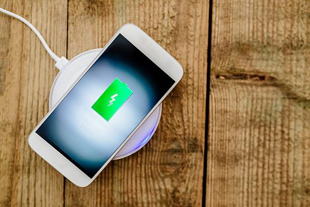 White smartphone charging on a charging pad. White smartphone charging on a charging pad. Wireless charging battery charger stock pictures, royalty-free photos & images