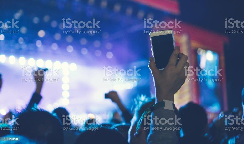 weißen Smartphone in der Luft am festival – Foto