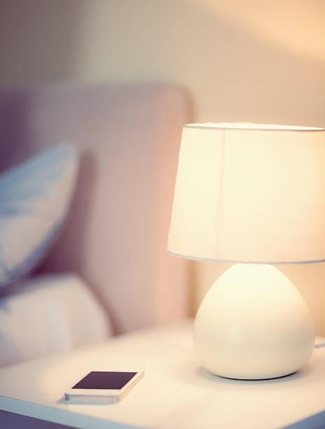 weiße smartphone entspannt auf dem nachttisch - nachttischleuchte stock-fotos und bilder