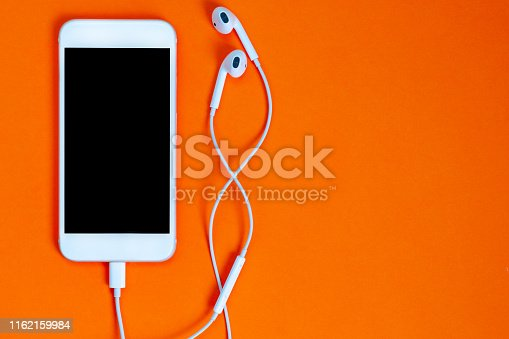 istock White smartphone on the orange background with headphones. View from above. 1162159984