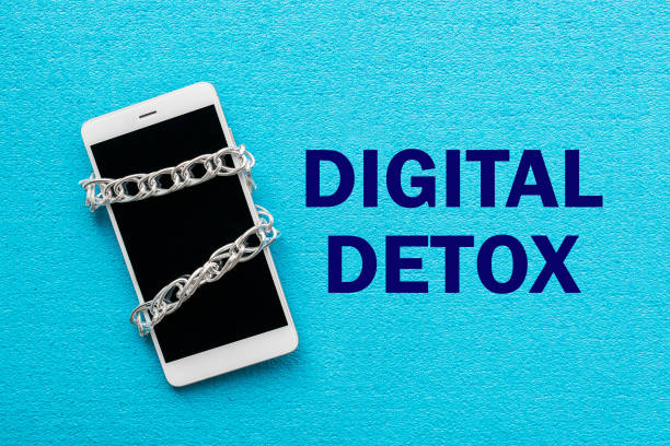 White smartphone with metal chain on blue background. Digital detox, dependency on tech, no gadget and devices concept White smartphone with metal chain on blue background. Digital detox, dependency on tech, no gadget and devices concept detox stock pictures, royalty-free photos & images