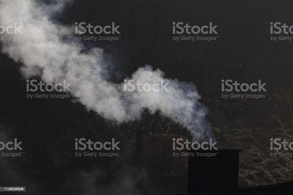 White smoking chimney with a dark background stock photo