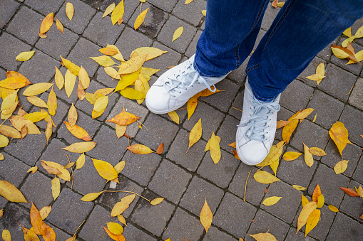 White sneakers on a street in autumn among the fallen yellow leaves.
