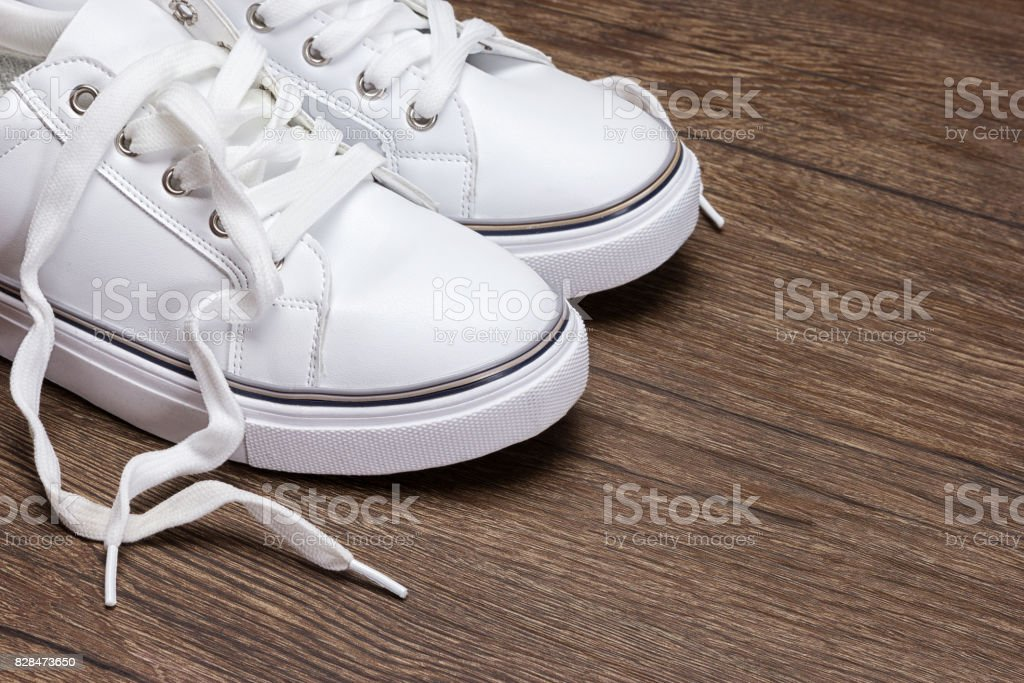 White sneakers on dark wooden surface stock photo