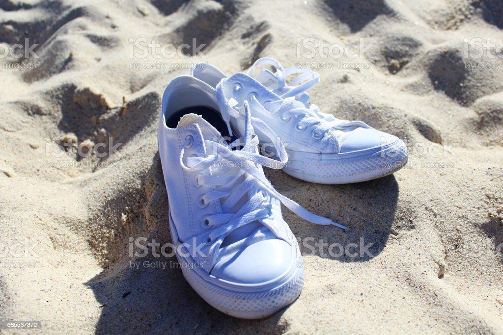 在沙灘上的白色運動鞋 免版稅 stock photo